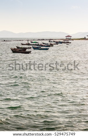 Beautiful sea, sand and fishing boats with mountain and blue sky in background at Phala Beach, Rayong, Thailand