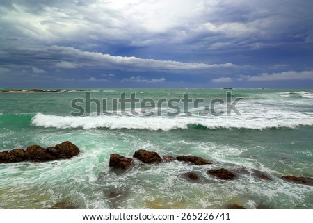Beautiful sea stormy landscape over rocky coastline in Indian ocean - stock photo