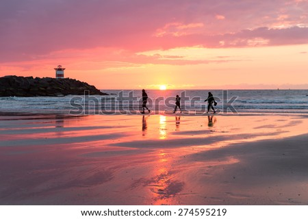 Beautiful sea sunset at Dutch coast near Scheveningen with passing hikers - stock photo