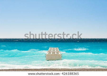 Beautiful sea with turquoise water and old pier on the beach. Nice, France