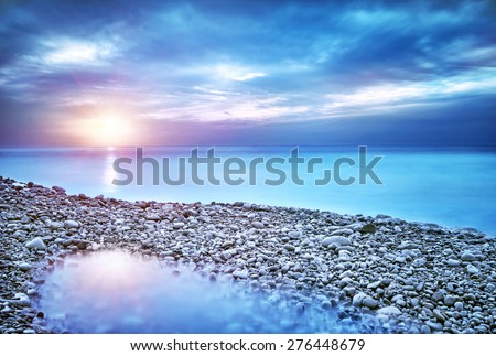 Beautiful seascape, amazing view of pebble coastline in mild sunset light, romantic evening on the beach, perfect place for summer holidays - stock photo