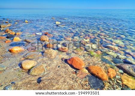 Beautiful seascape background with coastal stones in the ocean. The Baltic coast, mediterranean sea, Poland. - stock photo
