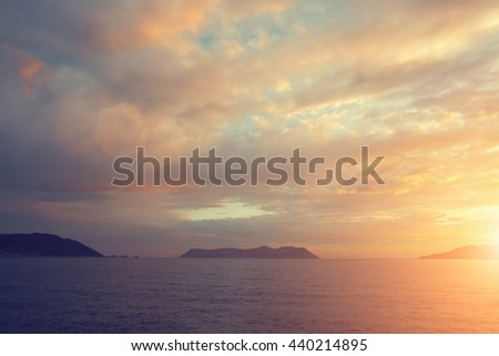 Beautiful seascape: calm water and the mountains in the distance at sunrise or sunset. Toned - stock photo