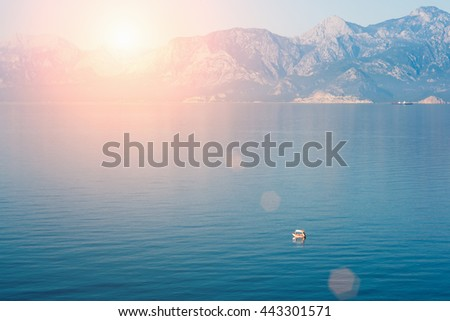 Beautiful seascape: calm water with boats and  high mountains in the sunlight. Toned