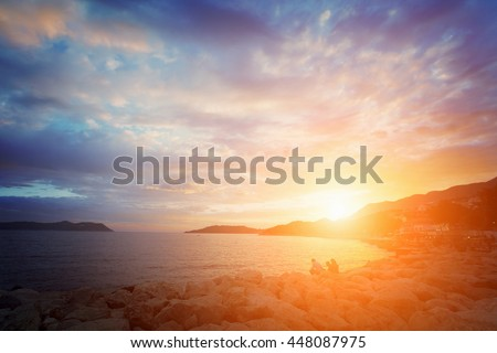 Beautiful seascape: people sit on the rocks by the sea at sunrise or sunset. Toned - stock photo