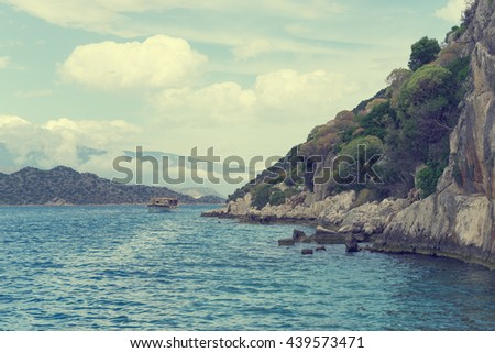 Beautiful seascape: rocky shore and the ship floating on the water. Toned