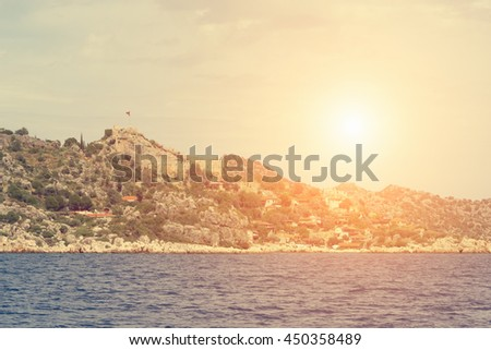 Beautiful seascape: ruins of an ancient fortress on a rock by the sea in the sunlight. Toned - stock photo