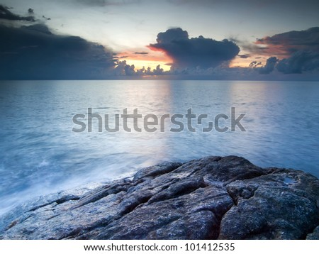 Beautiful seascape. Sea and rock at the sunset - stock photo