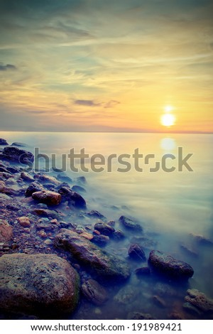Beautiful seascape. Sea and rock at the sunset. Vintage style