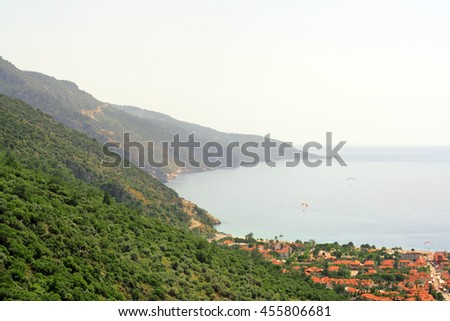 Beautiful seascape: sea, mountains and the paragliders flying over the city - stock photo