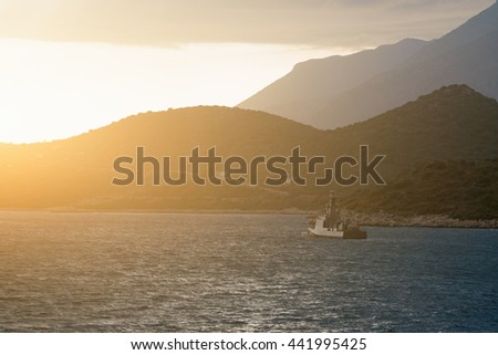 Beautiful seascape: ship floating on the water and rocky shore at sunrise or sunset - stock photo