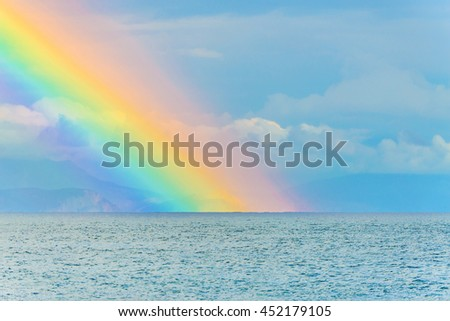 Beautiful seascape with big bright rainbow in clouds after the rain above the sea waves surface and mountains  - stock photo