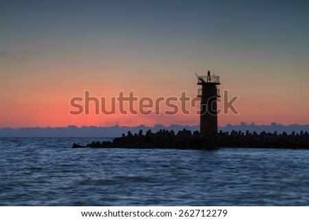 Beautiful seascape with lighthouse at sunrise. - stock photo