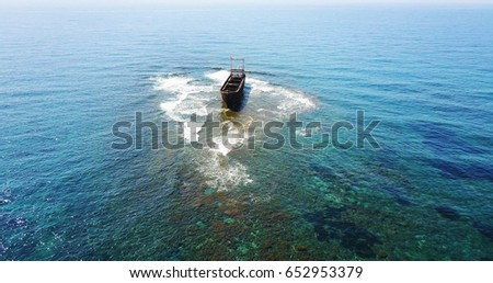 Beautiful seascape with old big, broken, rusty boat near the coast of Peyia, Cyprus. Ship graveyard. Famous landmark in the Mediterranean sea.
