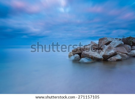 Beautiful seascape with stony breakwater photographed on long exposure. - stock photo