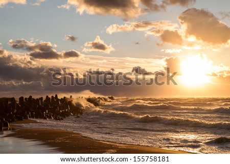 Beautiful seascape with water-break and splashes at sunset while windy and stormy weather on Baltic sea coast in Liepaja - stock photo