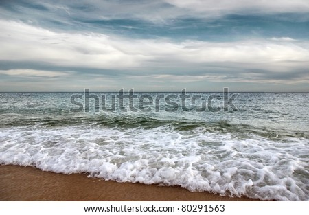 Beautiful seashore with calm waters and overcast sky - stock photo