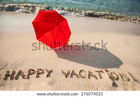 "Beautiful seashore with umbrella and ""Happy vacation"" drawn on  sand - stock photo"