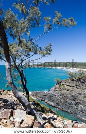 Beautiful, secluded, white sand beach in rocky shoreline, with eucalyptus tree, blue skies and calm tropical ocean; Noosa Heads National Park, Queensland, Australia. - stock photo