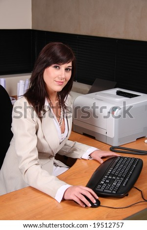Beautiful secretary at her desk with keyboard and mouse