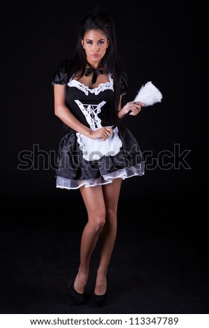 Beautiful seductive woman posing standing in a cute little maids outfit with miniskirt - stock photo