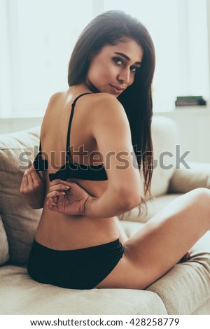 Beautiful seductress. Rear view of beautiful young mixed race woman in black lingerie looking over shoulder while sitting on couch and taking off her bra - stock photo