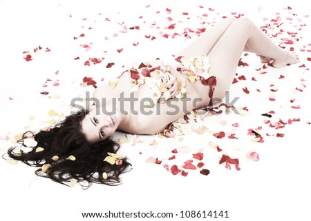 Beautiful semi naked brunette woman lying on white floor background on a bed of red orange and yellow rose petals with hair fanned out - stock photo