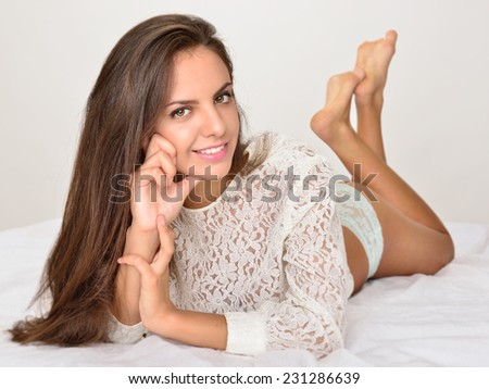 beautiful seminude woman with long hair laying on the white bed - stock photo