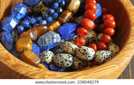 Beautiful semiprecious stone beads in wooden bowl - stock photo