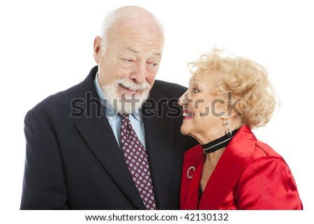 Beautiful senior couple dressed for the holidays, giving each other a knowing look of romance.  Isolated.