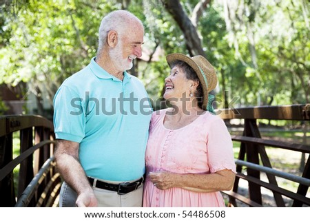 Beautiful senior couple flirting outdoors in the park. - stock photo