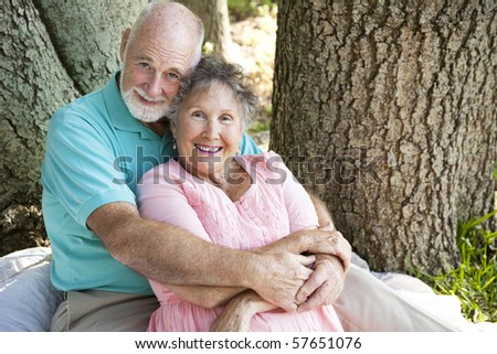 Beautiful senior couple in love, embracing under a tree. - stock photo