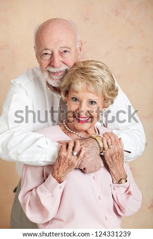 Beautiful senior couple in love, posing for a portrait in a close embrace.