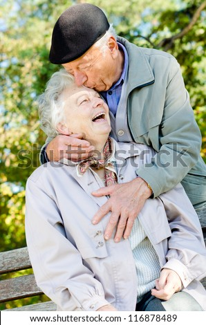 Beautiful senior couple kissing in autumn - stock photo