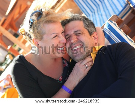 beautiful senior couple laughing on the beach - stock photo