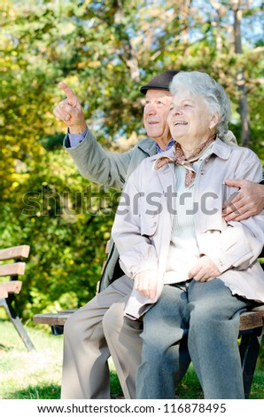 Beautiful senior couple looking to the sky - stock photo