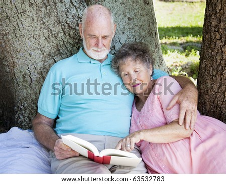 Beautiful senior couple reading together outdoors. - stock photo