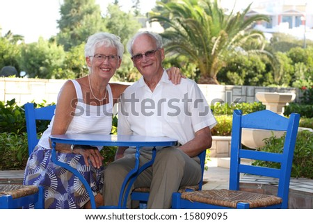 beautiful senior couple relaxing outdoors on a sunny day - stock photo