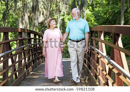 Beautiful senior couple stays fit by walking together in the park. - stock photo