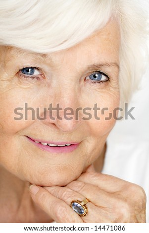 Beautiful senior lady portrait with hand on chin - stock photo