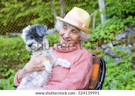 beautiful Senior smiling woman with straw hat  hugging her dog in the  mountain - stock photo