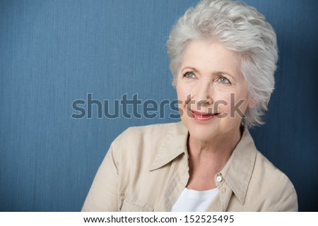 Beautiful senior woman daydreaming staring upwards with a gentle smile as she recalls nostalgic memories - stock photo