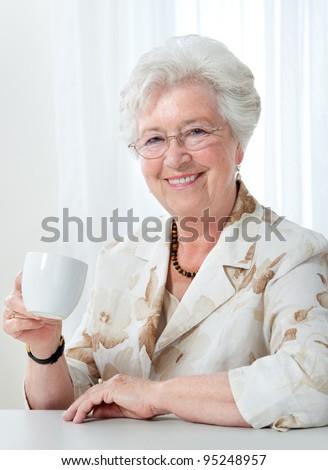 Beautiful senior woman enjoying a cup of tea or coffee - stock photo