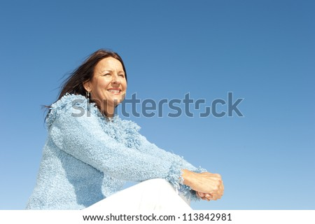 Beautiful senior woman enjoying relaxed sunny day, isolated with blue sky as background and copy space. - stock photo