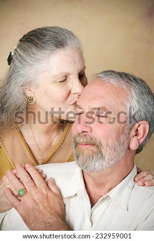 Beautiful senior woman gives her husband a loving kiss on the forehead.  Vignette added for dramatic effect.   - stock photo