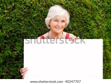 Beautiful senior woman holding blank board with space for text - stock photo