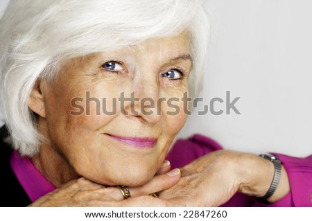 Beautiful senior woman holding chin on hands on grey background - stock photo