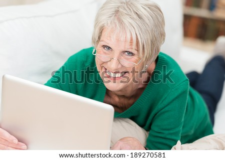 Beautiful senior woman wearing reading glasses lying on a sofa relaxing with her laptop computer smiling at the camera - stock photo