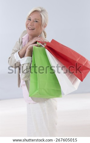 Beautiful senior woman with a lot of shopping bags - stock photo