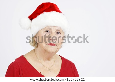 Beautiful senior woman with Santa Claus Christmas hat - stock photo